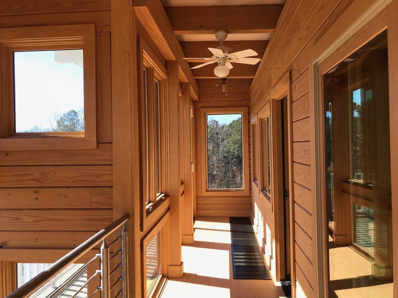Hallway and Medium Hardwood Floor Upper Guest Bedroom Sunspace and Deck  Meridian by Enertia Building Systems Inc.
