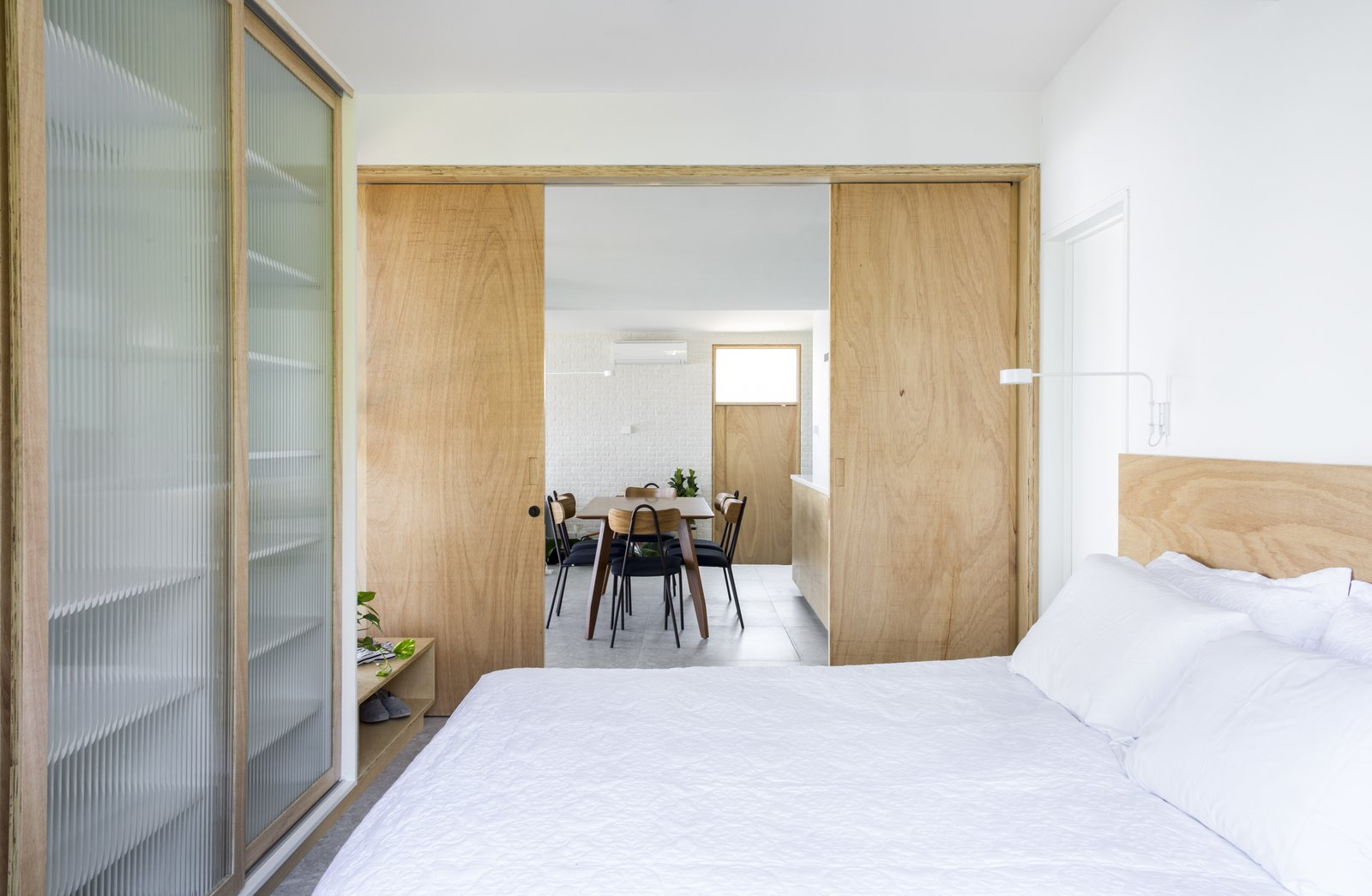 Bedroom, Bed, Porcelain Tile Floor, Ceiling Lighting, Floor Lighting, Wardrobe, Light Hardwood Floor, Wall Lighting, Dresser, and Bench designed by Estúdio Minke  Casa da Pedra (The stone house)