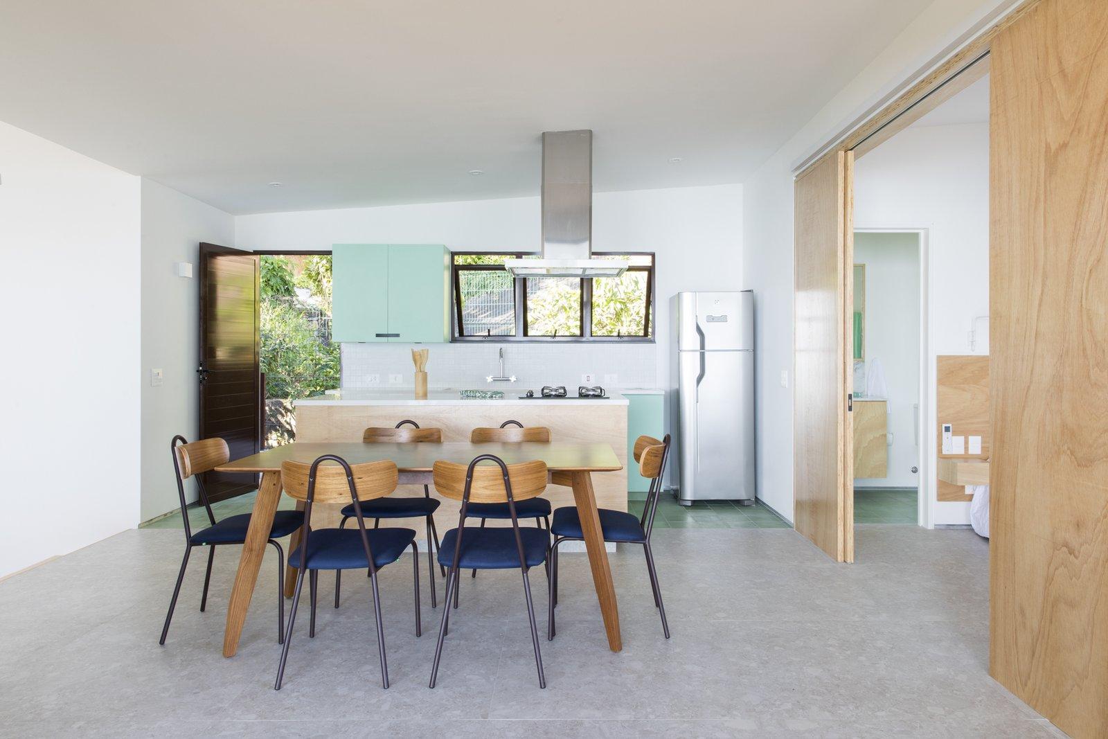 Dining Room, Table, Ceramic Tile Floor, Porcelain Tile Floor, Wall Lighting, Ceiling Lighting, and Chair designed by Estúdio Minke  Casa da Pedra (The stone house)