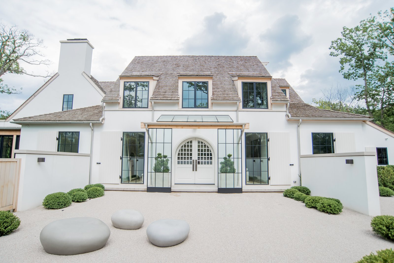 Exterior, House Building Type, Farmhouse Building Type, and Stucco Siding Material Home exterior features white stucco, cedar wood trim, custom black window frames and handmade front door from Poland.  Beautiful Belgian-inspired Farmhouse