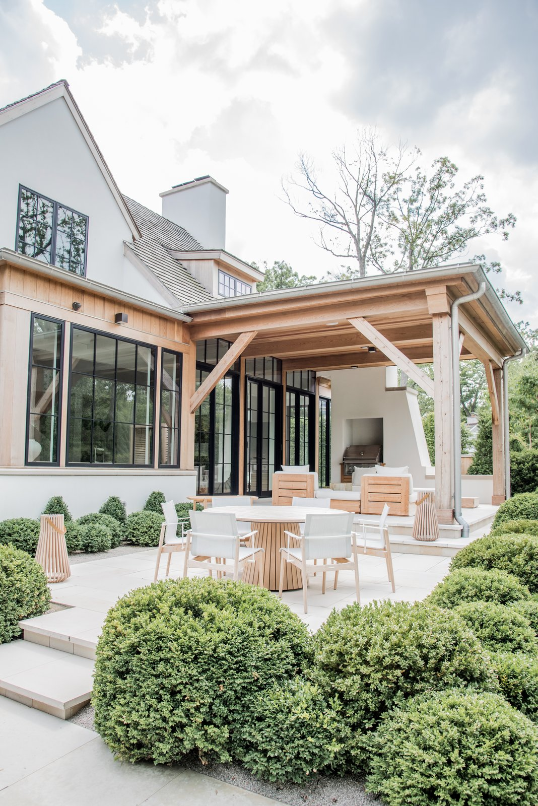 Outdoor, Back Yard, Concrete Patio, Porch, Deck, Trees, Large Patio, Porch, Deck, Gardens, Landscape Lighting, Grass, Shrubs, Garden, Planters Patio, Porch, Deck, and Walkways The indoor outdoor living is defined by large steel and glass doors that open to a covered barbecue area. The natural wood and white finishes are an extension of the home's interior design.  Beautiful Belgian-inspired Farmhouse