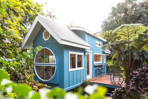 Oasis Tiny House, clad in teal-painted plywood and a metal roof that's pitched in the front and curved in the rear, was designed and built by Ellie and Dan Madsen of Paradise Tiny Homes in Keaau, Hawaii.