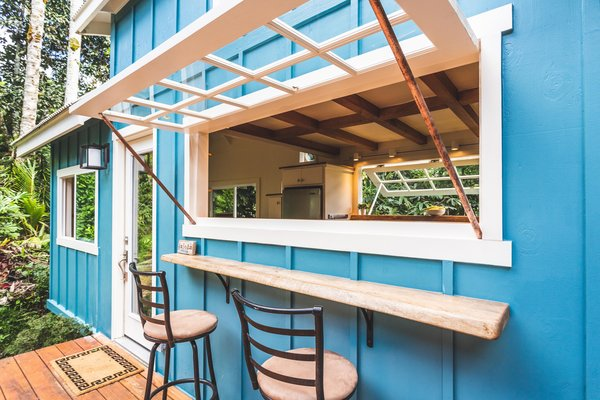 An outdoor deck and bar area with a mango wood counter and a massive window create an indoor/outdoor living experience.