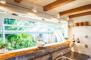 An elongated kitchen window ties the interior to the outdoor deck and bar area and the landscape beyond.