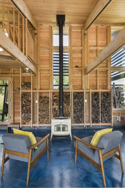 The owners' choice of a white wood stove influenced the architect's decision to dye the cement floor electric blue.