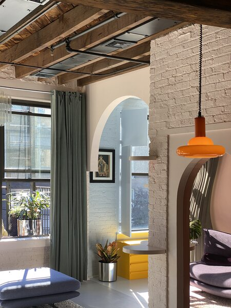 Antonio took down the wall between the living area and bedroom, then added an arch above the opening. The change in floor color from gray to pale blue also delineates the transition between spaces. He designed the built-in, arched mirror, too.