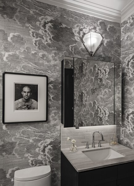 "In the bath, a portrait of English actor Joseph Fiennes by Herb Ritts hangs atop existing Cole & Son ""Nuvolette"" wallpaper by Piero Fornasetti, and the Gabriel Scott sconce relates to the chandelier in the dining room. O'Donnell added crown molding and designed a new vanity in the same style as the media console and new kitchen cabinet doors."