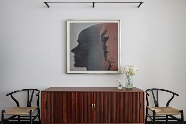 """Andy Warhol, The Shadow (FS II.267), 1981 from the artist's Myths series hangs above a vintage teak credenza that O'Donnell added to anchor the photograph and bring warmth to the space. """"We worked together to find pieces that related to what he already had,"""