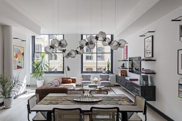 """Linear black picture lights by Juniper showcase the artwork and brighten the whole length of the apartment. """"The lights are a nod to a traditional way of highlighting art but feel very modern,"""" O'Donnell says."""
