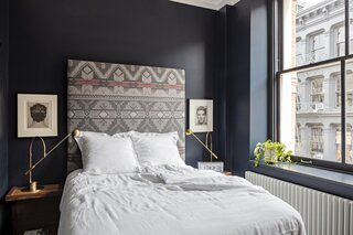 """Front- and back-of-head portraits by Cuban photographer Jose Picayo from the Robin Rice Gallery in the West Village flank the headboard upholstered in Ralph Lauren fabric. """"It's inspired by the tall headboards at the Crosby Hotel,"""" Marc says. The walls are painted Benjamin Moore Polo Blue."""