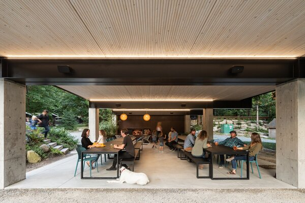 Long black metal tables and benches from Case Furniture's EOS collection populate the underbelly of the building, which became a dining pavilion.