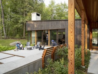 """DiNiord collaborated with craftsman Ken Hood to design the concrete bench with firewood storage and detachable wood back. Douglas fir columns along the walkway creates a colonnade. The mono-sloped roof is a nod to the long roofline of the original house that stood on the property. """"Reducing the angles also reflects the strictness to budget,"""" the wife says."""