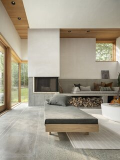 """Interior designer Heidi Lachapelle chose unfussy furnishings with clean lines. """"Nothing should feel decorative or unnecessary,"""" she says. """"We looked for things that would age beautifully to speak to the wabi-sabi concept."""" The oak daybed is by Bautier, the indoor/outdoor rug is by Dash & Albert, and the trapezoidal cushions on the concrete bench nod to similar ones that the wife saw at Georgia O'Keefe's home and studio. The Scandinavian-inspired fireplace throws heat from two sides."""