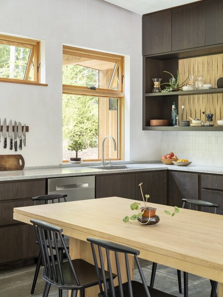 The tile backsplash matches the wall color, though it differs in texture, and the countertop is made from local granite. The light-colored wood screen set at the back of the darkly stained cabinetry mirrors the dark outside and light inside of the exterior facade.