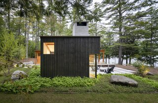 """While the owners really liked the idea of shou sugi ban, they opted for a more cost-effective black stain. The random-width, reverse board-and-batten siding reflects the wabi-sabi concept. """"The builder said the math for the random siding was torturous,"""" the wife said. """"We didn't know how hard it was to make things look simple."""" DeNiord planted hay-scented fern and lowbush blueberry sod around the house. """"We didn't want any side of the house to feel unconsidered,"""" he says. As for the local boulders he placed around the house and terrace, he says, """"They give the feeling that the house grew up around the outcroppings."""""""