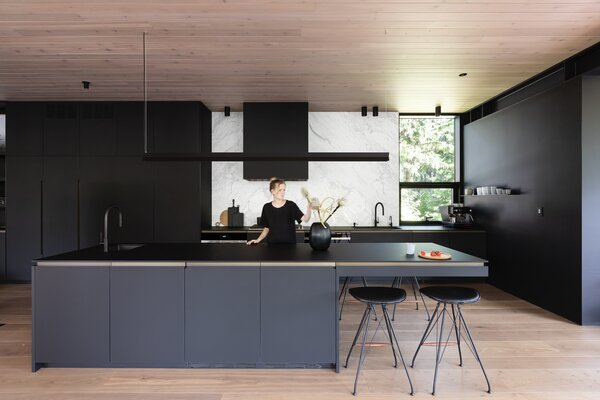 """The linear suspension pendant by Michael Raasch provides up and down lighting over the island. Like the cabinetry, the countertop is also done in Fenix. """"The owner liked the idea of consistency,"""