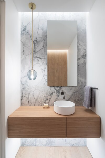 The stone was the driving force behind the powder room design. The grey glass of the custom Lindsey Adelman light connects to the veining and elevates the whole look.