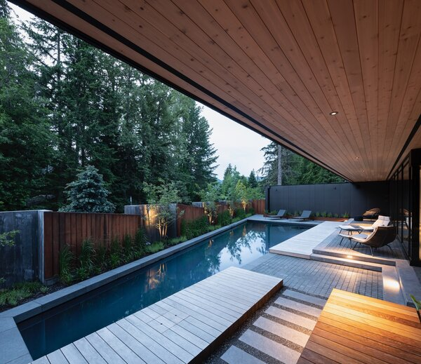 Angled, sloping pickets function like Venetian blinds between the board-formed concrete volumes and tall vertical grasses provide another layer of screening.  An ipe deck with a waterfall design runs parallel to the pool.
