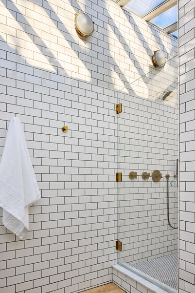 White subway tile with charcoal-colored grout covers the primary bath where sunlight streams in from overhead thanks to a huge, new skylight. Wall sconces from The Urban Electric Co. lend a nautical feel.