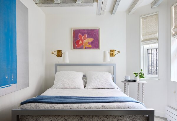 The owner's 23-year old daughter sleeps ere when she visits from the West Coast. The flower painting above the bed is her childhood artwork and the blue painting is by New York City artist John Zinsser.