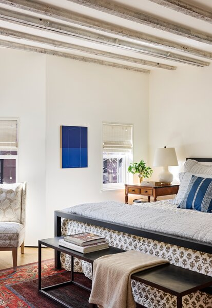 """The primary bedroom has small windows but lofty ceilings with original exposed beams. The comforter is from Out of Hand in G<span style=""""font-family: Theinhardt, -apple-system, BlinkMacSystemFont, &quot;Segoe UI&quot;, Roboto, Oxygen-Sans, Ubuntu, Cantarell, &quot;Helvetica Neue&quot;, sans-serif;"""">reat Barrington</span><span style=""""font-family: Theinhardt, -apple-system, BlinkMacSystemFont, &quot;Segoe UI&quot;, Roboto, Oxygen-Sans, Ubuntu, Cantarell, &quot;Helvetica Neue&quot;, sans-serif;""""> , Massachusetts, the table lamp is by Christopher Spitzmiller, and the vintage rug came from a dealer in Cleveland . With her daughter's help, Priscilla carried the (</span><span style=""""font-family: Theinhardt, -apple-system, BlinkMacSystemFont, &quot;Segoe UI&quot;, Roboto, Oxygen-Sans, Ubuntu, Cantarell, &quot;Helvetica Neue&quot;, sans-serif;"""">since reupholstered) </span><span style=""""font-family: Theinhardt, -apple-system, BlinkMacSystemFont, &quot;Segoe UI&quot;, Roboto, Oxygen-Sans, Ubuntu, Cantarell, &quot;Helvetica Neue&quot;, sans-serif;"""">Jonathan Adler chair home from his shop on Atlantic Avenue. """"The store was closing, so the chair was so cheap that having it delivered would have cost more than the chair itself,"""