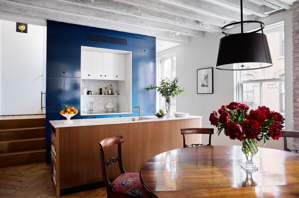 """The kitchen and dining area share the parlor level. The stair runs behind the blue core and the kitchen appliances are tucked into it. Priscilla finds the kitchen more efficient than her prior, much larger kitchen. """"It's amazing how little you need,"""
