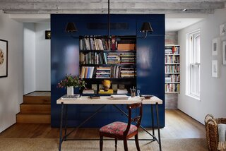 """Priscilla and McBride initially discussed the office core being an actual desk that could be closed, but opted for this setup so she could sit with her back to the books and look out the window. The double arm chandelier from The Urban Electric Co. lends a sturdy, industrial feel that echoes the metal base of the desk. """"Light fixtures are an important details that make a house feel solid,"""