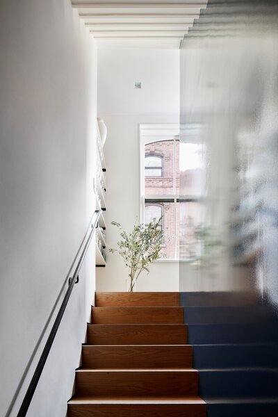"""The stairs are hidden behind a core wood block with a high gloss finish for a mirror-like reflection. Fortuitously, there is a window at the top of each run. """"They're not perfectly aligned, but they bring light down at every level,"""
