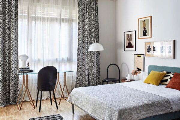 """Alexandrine describes the second bedroom as """"a functional space for a grown-up girl student.""""  On the wall, prints by Olga Fradina are mixed with vintage graphics from the 1960s. A lamp from the 1970s sits atop a modern italian writing desk."""