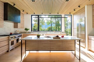 """Local cabinetmaker Peter Pomerantz made the custom, white oak cabinetry and Flywheel Industrial Arts fabricated the steel hood. """"It's about lines and shadows; no hardware,"""" Herrmann says."""