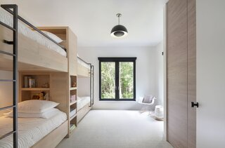 """Herrmann's first inclination was to design the bunks without a partition between them, but the owners asked that each one be its own little pod complete with bookshelves and reading light. """"The kids love the bunk room,"""" the husband says. """"At home, the twins share a room and their baby brother is the odd man out. Here, for twelve weeks, he gets to be a part of it."""""""