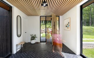 """The oversized, oak pivot door has a hefty feel. """"It's about the tactile qualities and the craft,"""" Herrmann says. Slate tile with a clef finish in a herringbone pattern connects the entryway to the outdoors. The abstract painting is by British Columbia-based artist Andrea Soos."""