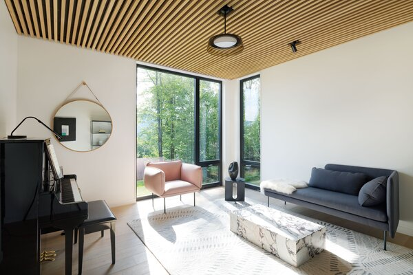 """A music room was a must-have for the owners. """"My wife plays piano an hour a day, and I like to play records,"""" the husband says. """"The kids know this is mom and dad's room."""" The seating is by Blu Dot."""