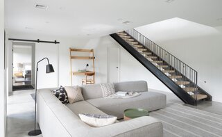 The lower level, which has a polished concrete floor and comfy Blue Dot sectional, is where the kids run around, do craft projects, and watch television. A plain barn door separates this area from the guest suite. There are also sliders that spill out into the yard.