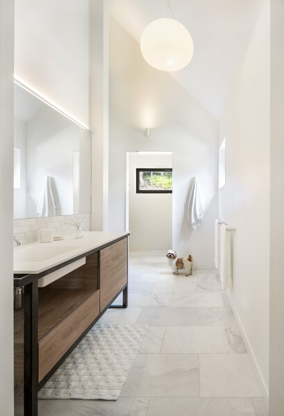 The primary bath has a custom vanity and a textured tile backsplash.