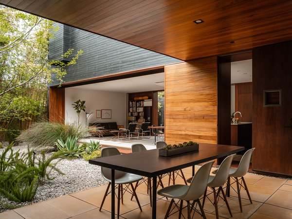 Today, a California live oak blocks a view from the street, and a massive pine sits in the front courtyard—in addition to a Japanese maple, bamboo, and other specimens. Here is a look into the second courtyard and a covered patio off the kitchen.