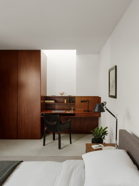 One of the guest bedrooms is illuminated by a skylight in the corner, above a built-in desk.