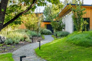A gravel trail winds through greenery into the entryway of the home, reinforcing the parklike nature of the site.