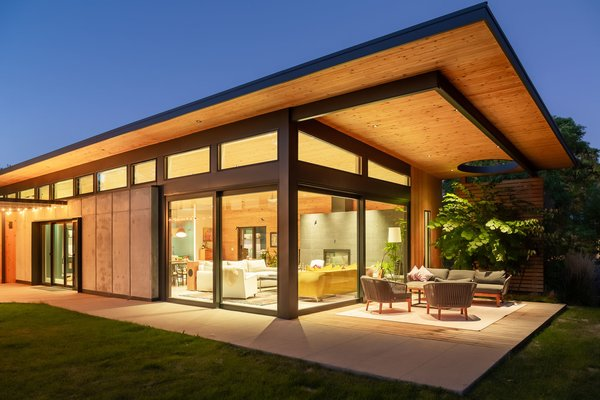 As night falls, the home lights up like a lantern, enhancing the warm glow of the wood ceiling. Immense clerestory windows and glass sliders connect the home to the outdoors.