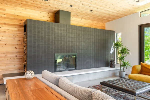 An imposing, matte black fireplace is the focal point of the living room. Wood is stored within the structure, which frees up floor space for abundant guest seating.