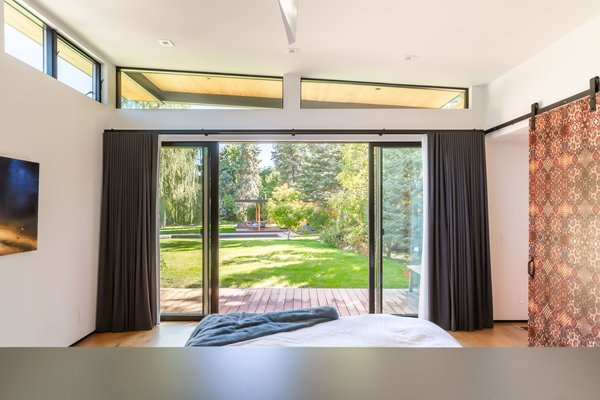 The master bedroom gazes upon a rolling lawn and lush pine trees. One of many patio spaces can be seen across the grass.