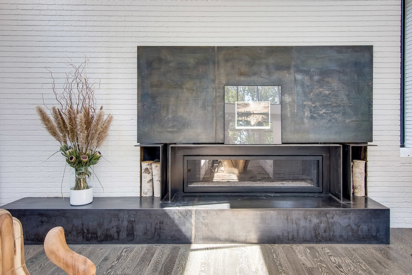 Living Room, Dark Hardwood Floor, Ribbon Fireplace, and Recessed Lighting Dramatic steel panels slide open to reveal the TV over the long fireplace and steel mantel  Modern View
