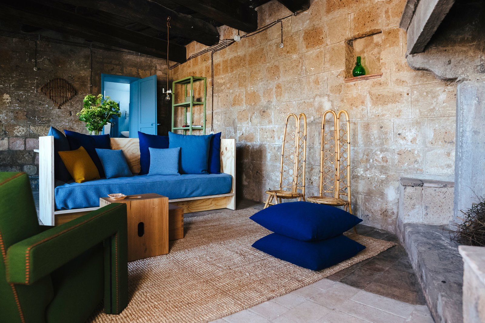 Living Room, Sofa, Console Tables, Ottomans, Wood Burning Fireplace, and Limestone Floor The designers decided to keep the original stone walls and floors.  Photo 9 of 20 in Italian Ghost Towns Are Turning Abandoned Buildings Into Alluring Airbnbs from Design apartments in Italian ghost towns