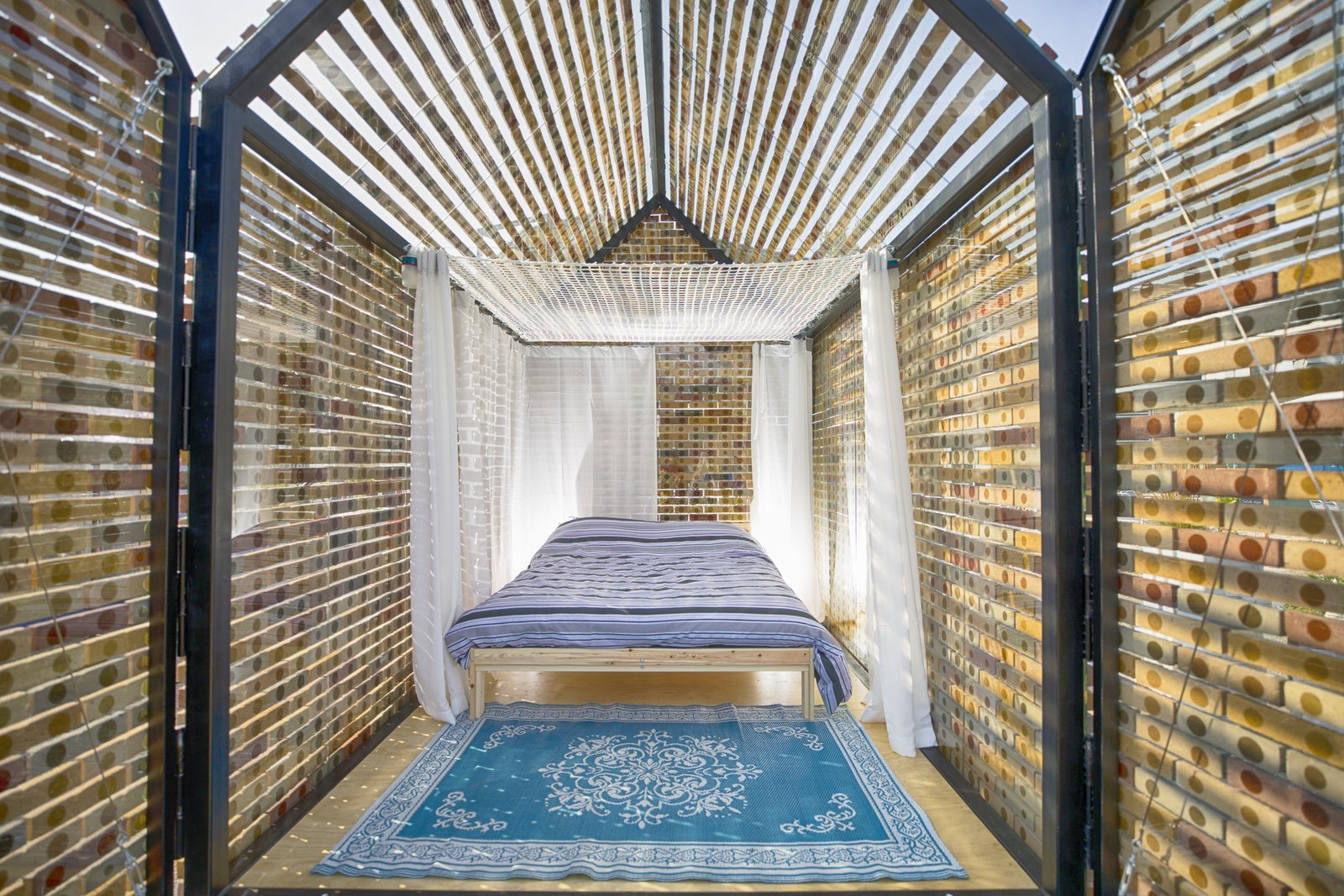 Bedroom, Bed, and Rug Floor Floating Bricks is a tiny cabin that sleeps three people; a comfy hammock can be hung above the double bed.  Photo 9 of 15 in At This Quirky Campsite in Rotterdam, You'll Sleep in Upcycled Grain Silos and Calf Igloos from Culture Campsite Rotterdam