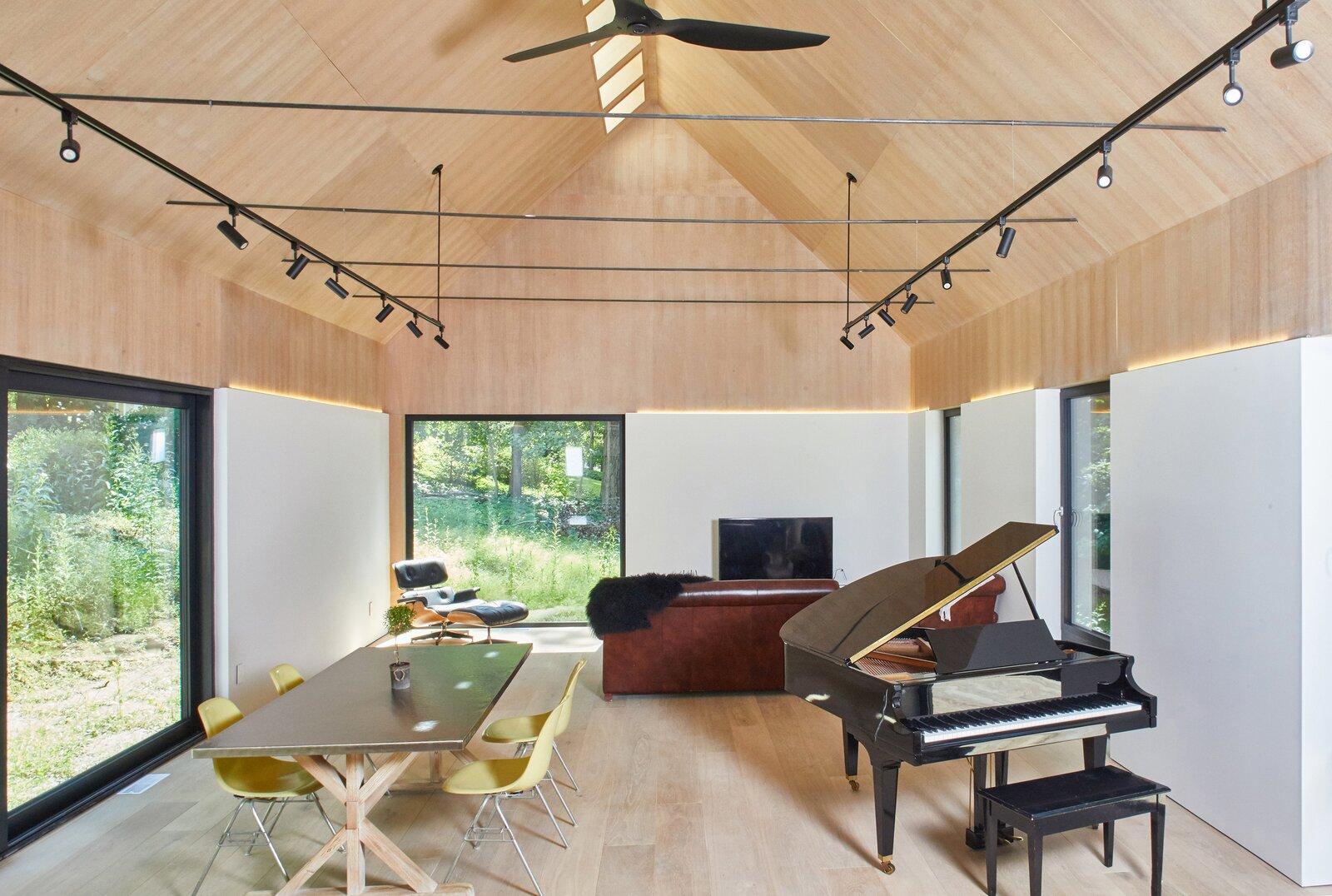 Living Room, Sofa, Track Lighting, Light Hardwood Floor, Chair, Accent Lighting, Ottomans, and Plywood Floor Great Room  Cork Haven by Multitude Studio