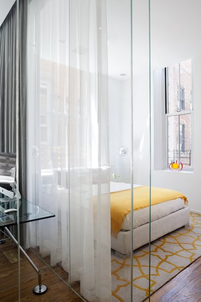 Tom Dixon Mirror Ball lights and a Flou Italia bed soak up sunlight in the guest room.