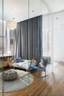 Designer Nina Blair's Tribeca loft features a former glass-box office that has been turned into a kids' room with a wraparound curtain for privacy. In the morning, she explains, the kids draw the curtains open to reconnect with the rest of the home.