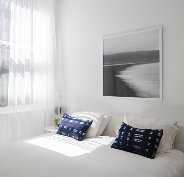 """Nina's goal in the bedroom was to create a """"simple, soothing"""" space with a focus on light. Handmade indigo pillows from Mali and a tranquil beachscape photograph taken in Iceland embody the nature-inspired connection between African and Scandinavian design."""