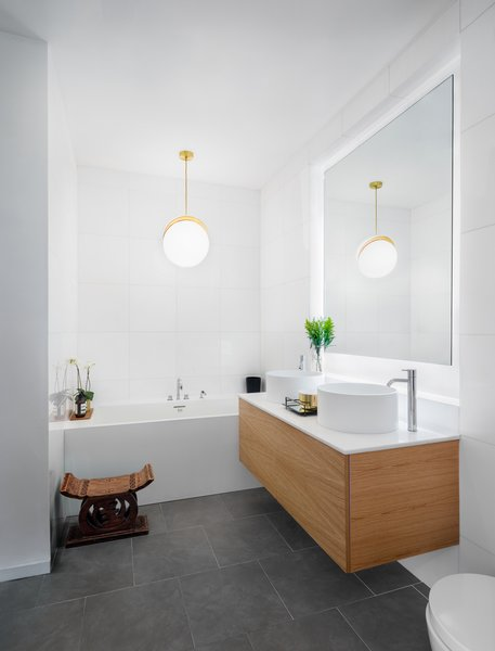 "An Ashanti stool that was ""a wedding gift from the designer's family"" rests beside a Wetstyle tub. Hanging above is a Crescent Light by Lee Broom."