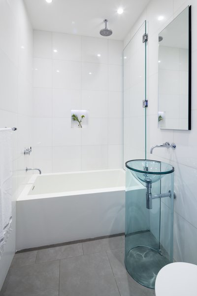 A second bathroom maintains the open brightness of the rest of the loft with simple white tiling and a transparent pedestal sink.